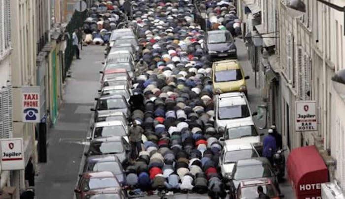 Muslims at prayer in a European street.
